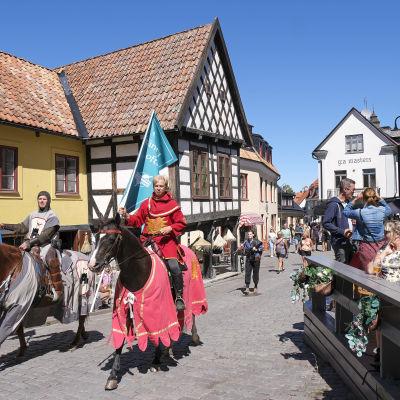Två riddare på häst rider igenom Visby med flaggor som uppmanar turisterna att hålla avstånd.