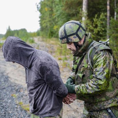 sotilas ottaa vangin kiinni harjoituksessa