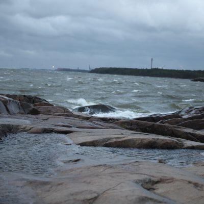 Myrskyävä meri ja kallioista rantaa.