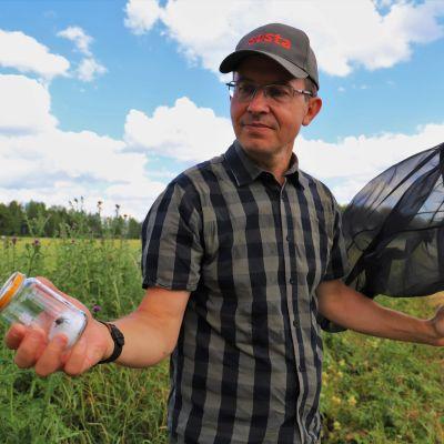 En man står utomhus med en håv i ena handen och en glasburk i den andra