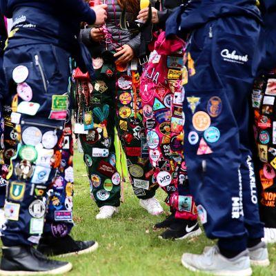 Studerande klädda i studenthalare står i klunga ute i parkmiljö.