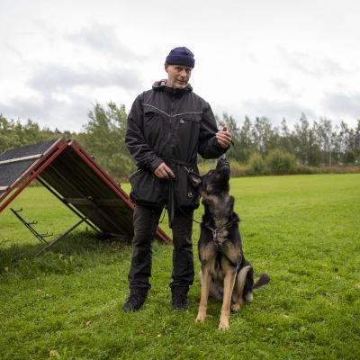 SPL-Kouvolan puheenjohtaja Petri Rautio poseeraa koiransa koirien harjoituskentällä