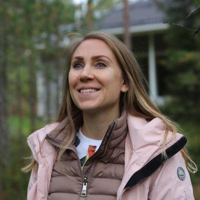 Evelina Lorek seisoo metsässä Rovaniemellä. Taustalla näkyy talo