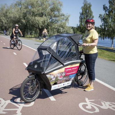 Toimittaja Tanja Perkkiö esittelee kuomullista taakkapyörää pyörätiellä.