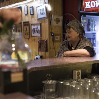 Jämijärveläinen Marja-Liisa Vartio istuu baarissaan tiskin edessä.