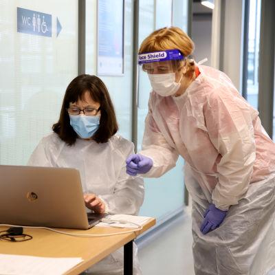 sairaanhoitajat Sylva Lallukka ja Mirjam Koutonen katsovat tietokonetta Vaalimaan raja-asemalla