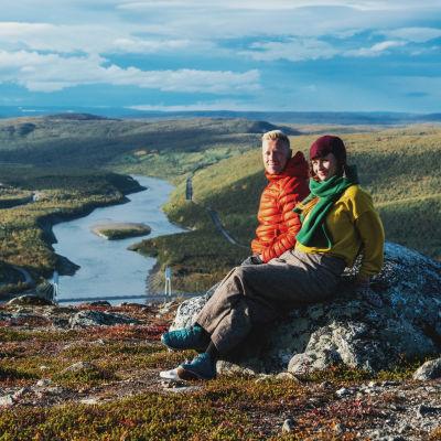 Kvinna och man sitter på en sten uppe på ett fjäll och njuter av solskenet, i bakgrunden ett fjällandskap med en älv i mitten.