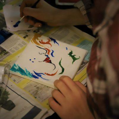 Alva Fontell maalaa. Kuvan naien kasvoilla on kolme maalitahraa.