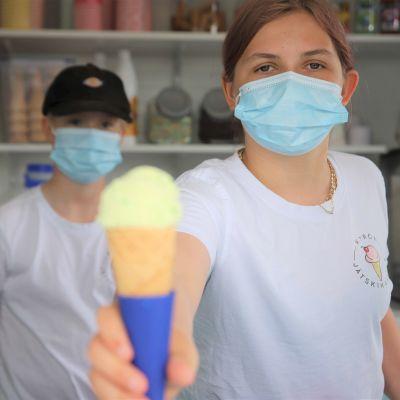 Tyttö tarjoaa jäätelötuuttia jäätelökioskista