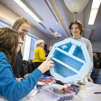 Oppilaita tutkimassa tutkimuslaitetta, joka lähetetään avaruuteen