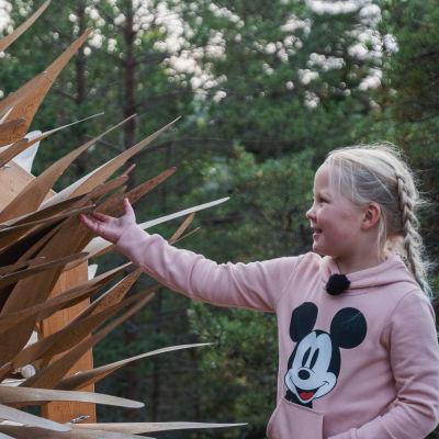Nellie Wallden koskettaa suurta, puusta tehtyä taideteosta, jossa on liikkuvia siipimäisiä ulokkeita.