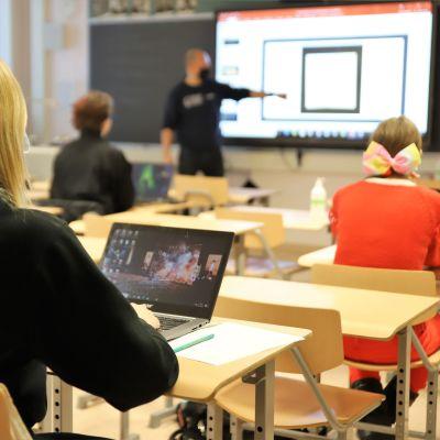 Abiturienter sitter i ett klassrum och lyssnar på en lärare som pekar på något.