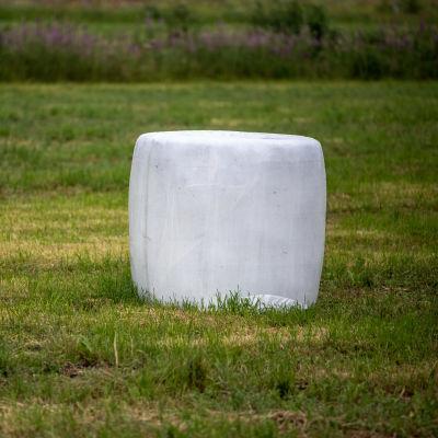 Valkoinen heinäpaali pellolla.