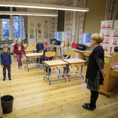 Hajalan koulun 1.-2.-luokkalaiset seisovat luokassa pulpettien vieressä Hajaln koulussa.