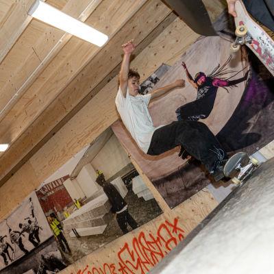 Ruu Ahlstedt skeittaa kaaressa vaneri seinien ympäröimänä. Seinillä on isoja valokuvia skeittihallin rakennusvaiheista.
