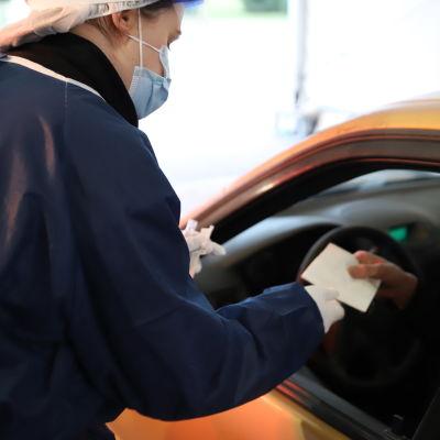 Sairaanhoitaja ojentaa autossa istuvalle asiakkaalle paperin.