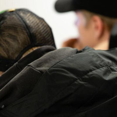ungdomar i märka kläder och mörka kepsar sitter nedhukade