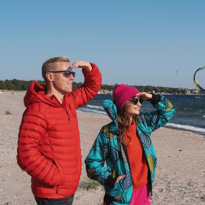 Egenandin juontajat Nicke Aldén ja Hannamari Hoikkala katselevat aurinkoisena päivänä Tulliniemen rannan purje- ja leijalautailijoita.