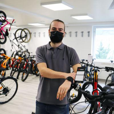 Aleksi Sanaksenaho står bredvid cyklar i en cykelaffär.