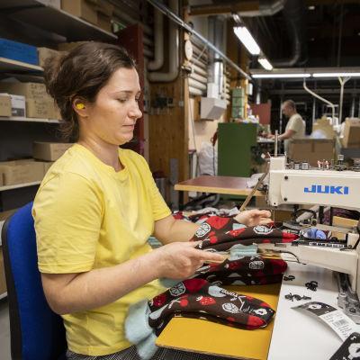 Olga Davydenko kiinnittää lappuja sukkiin Teseman tehtaalla.