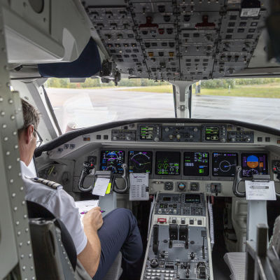 En person sitter i förarens plats i ett flygplan.