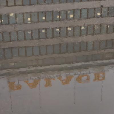 EK:s fasad speglar sig i en grå vattenpöl i regn.