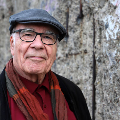 En äldre man med en skärmmössa på huvudet, glasögon, röd skjorta, svart kavaj och en färggrant rutig halsduk i orangenyanser tittar vänligt, men bestämt in i kameran. I bakgrunden är en grå mur.