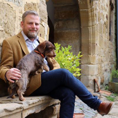 Karl Schenk Graf von Stauffenberg, en medelålders man, sitter med en hund i famnen på en bänk.