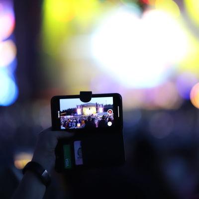 En mobil hålls upp i ett publikhav och filmar ett framträdande under Pori Jazz 2019.