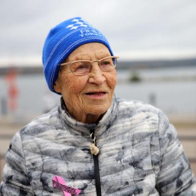 Siiri Rantanen istuu penkillä pipo päässä Vesijärven satamassa, järvi taka-alalla.