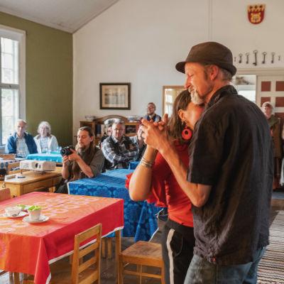Olli Soini ja Anni Paunula tanssivat Keltainen talo -kulttuurikeskuksessa Janakkalassa, taustalla salissa muita kuuntelijoita.