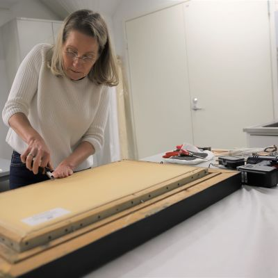 Taidekonservaattori Nina Robbins vaihtaa maalaukseen kiilakehystä