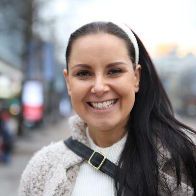 Nuori nainen hymyilee lähikuvassa kadulla