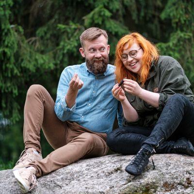 Joakim Lax och Annika Ljungberg sitter på en sten och tittar på något litet.