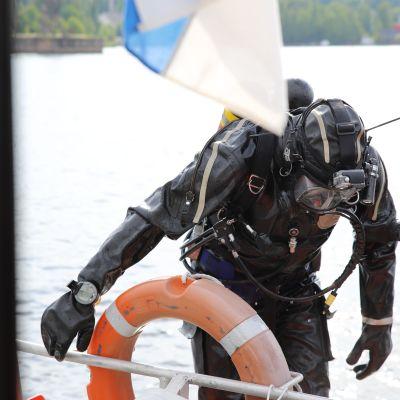 Palomies Kalle Koskela Kymenlaakson pelastuslaitokselta kiipeämässä veneeseen sukelluksen jälkeen.