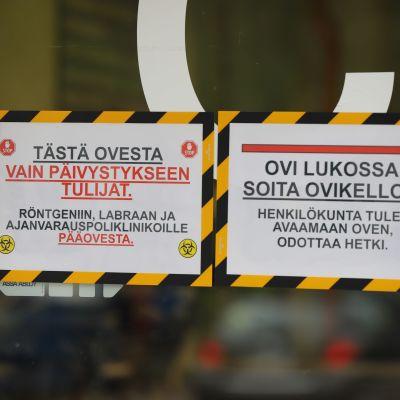 Pohjois-Kymen sairaalan Infektiovastaanoton ovella huomiolappuja.