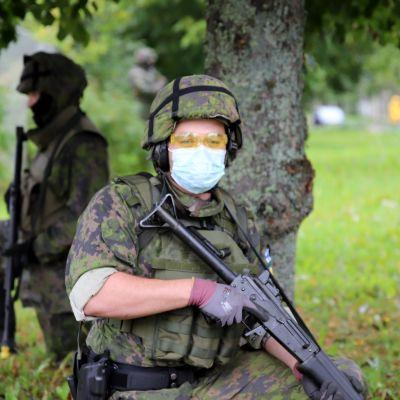 Sotilas vartiossa polvillaan aseen kanssa puun juurella, taustalla toinen sotilas