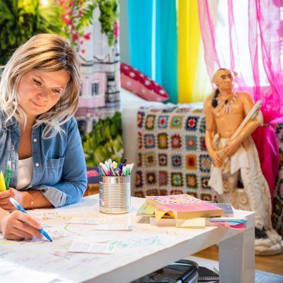 Saana Alanko istuu pöydän ääressä olohuoneessa ja piirtää paperille.