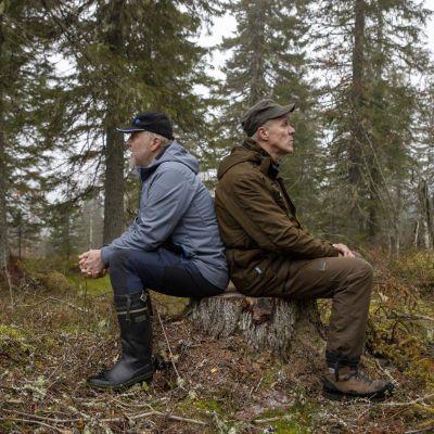 Arto Tolonen ja  Ahti Juntunen istuvat seläkkäin kannolla.