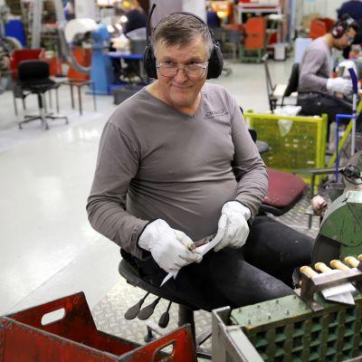 Olavi Kallatsa on mestari teroittamaan puukkoja, istuu työkoneen äärellä kuulokkeet korvilla, puukko kädessä jolla suikaloi paperia.