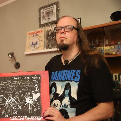Jari-Pekka Laitio-Ramone pitelee kädessään Dee Dee Ramonen maalaamaa taulua.