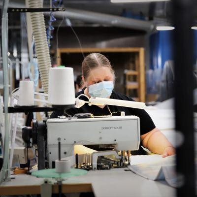 Päivi Harjuhahto ompelee peittoja Lennolin tehtaalla.