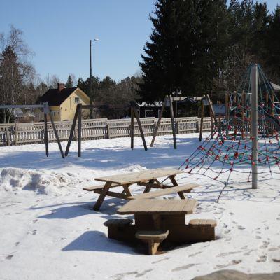 Keinuja ja köysiteline sekä muita lasten leikkivälineitä päiväkodin pihalla autiona