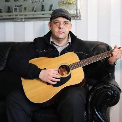 Tino Zitron istumassa sohvalla kitara käsissään.