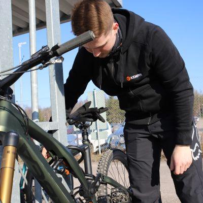 Jukka Lammi kiinnittää polkupyöräänsä lukkoa.