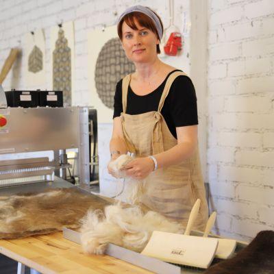 Nainen laittaa huovutuskoneeseen pöydällä lojuvia kasoja hiuksia ja läinen karvoja