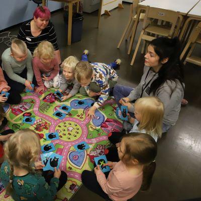 Dagisbarn och dagispersonal sitter på golvet vid en bilbana.