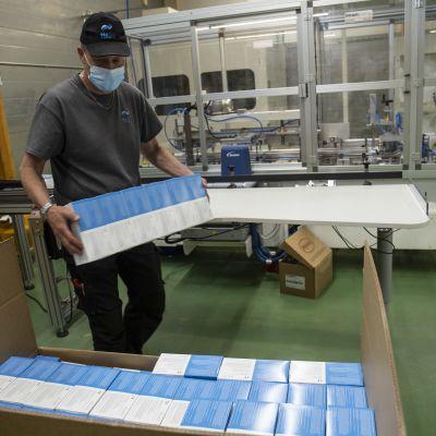 En anställd packar förpackningar med munskydd.