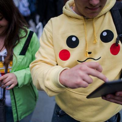 Två ungdomar spelar mobilspel. Den unga mannen bär en Pokémon Go-tröja.