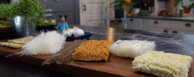 Olika nudlar på en skärbräda i ett kök